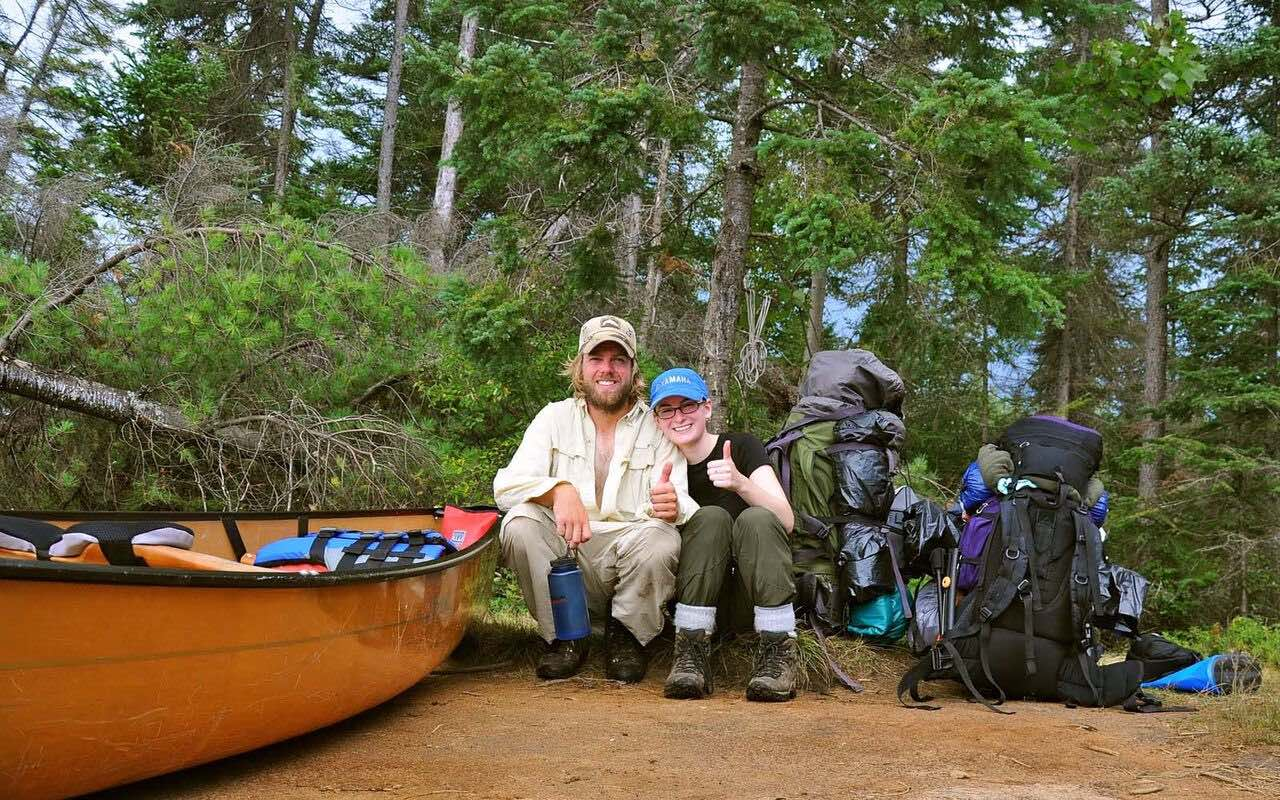 Young couple resting during canoe trip in Algonquin Park with Algonquin Outfitters