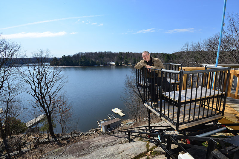 Alvin Allen of Cottage Lifts Elevation solutions on lift near lake