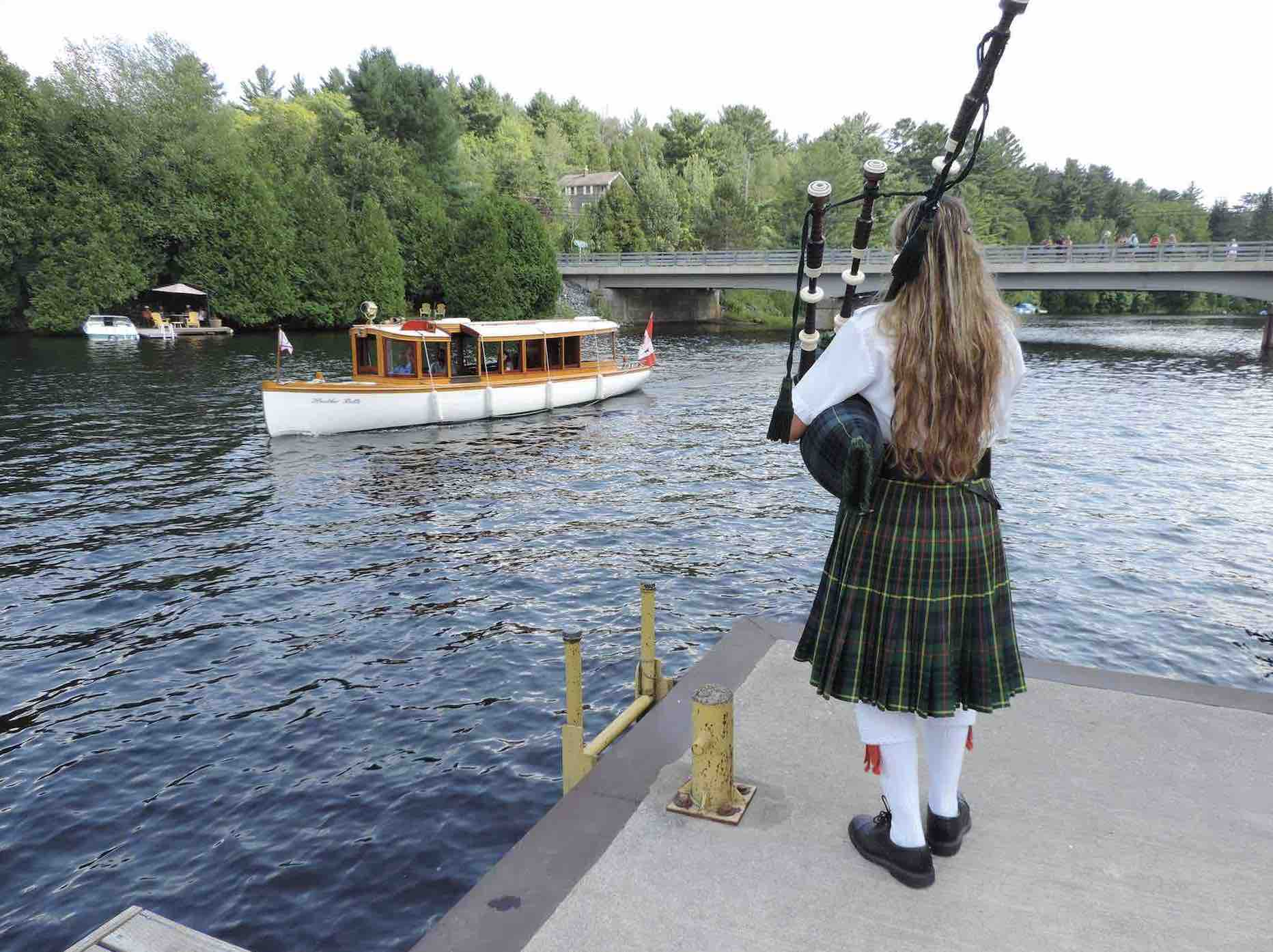 The Marvellous Lake of Bays Antique Boat Show with antique boats and bagpiper on dock