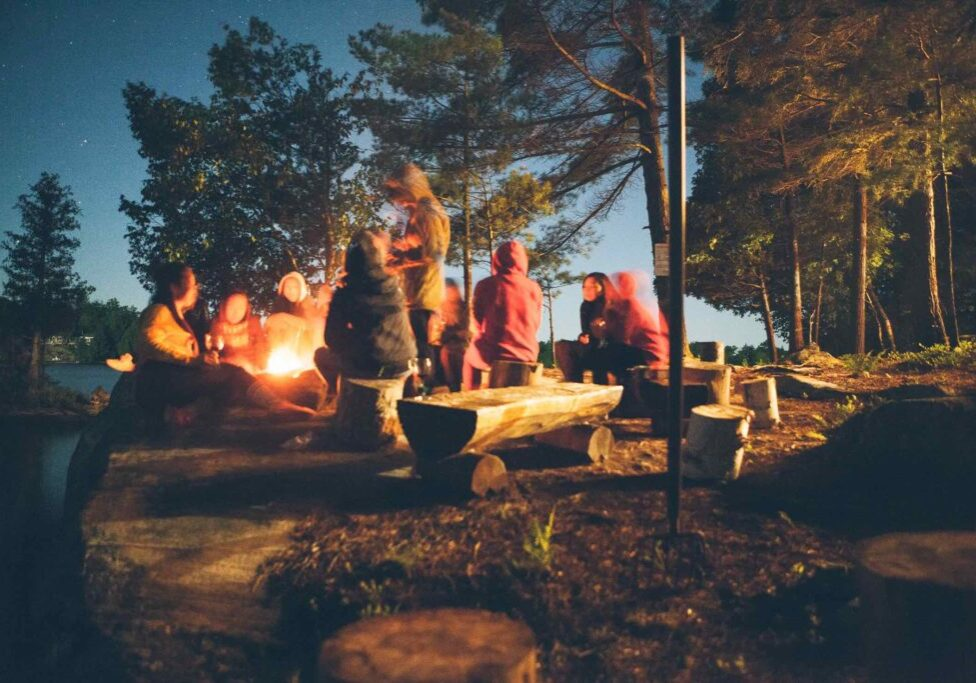 Family and friends at a lakeside campfire in Muskoka Lakes